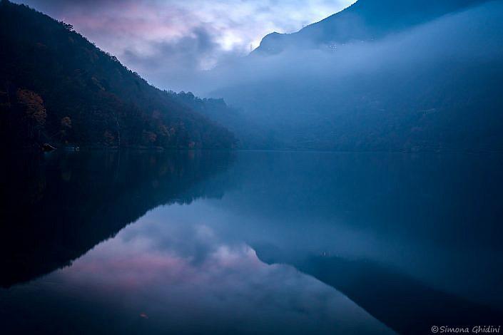 Fotografia di paesaggi con il lago moro nella nebbia sul far della sera