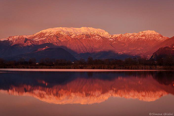 Fotografia di paesaggi al tramonto con monte guglielmo innevato illuminato e riflesso nell'acqua alla riserva naturale torbiere del sebino