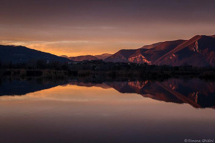 Fotografia di paesaggi al tramonto con montagne che si specchiano nell'acqua alla riserva naturale torbiere del sebino