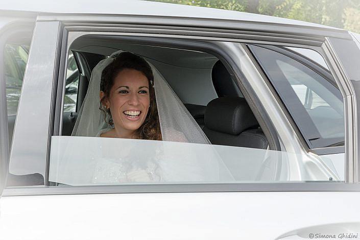 Servizio fotografico per matrimonio con arrivo sposa sorridente in macchina
