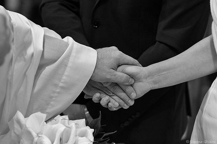 Servizio fotografico per matrimonio con mani unite di sposi e prete