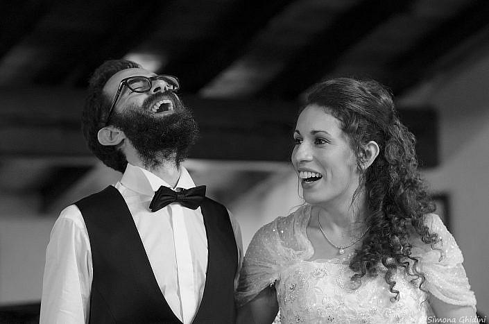 Servizio fotografico per matrimonio con risate degli sposi al ricevimento